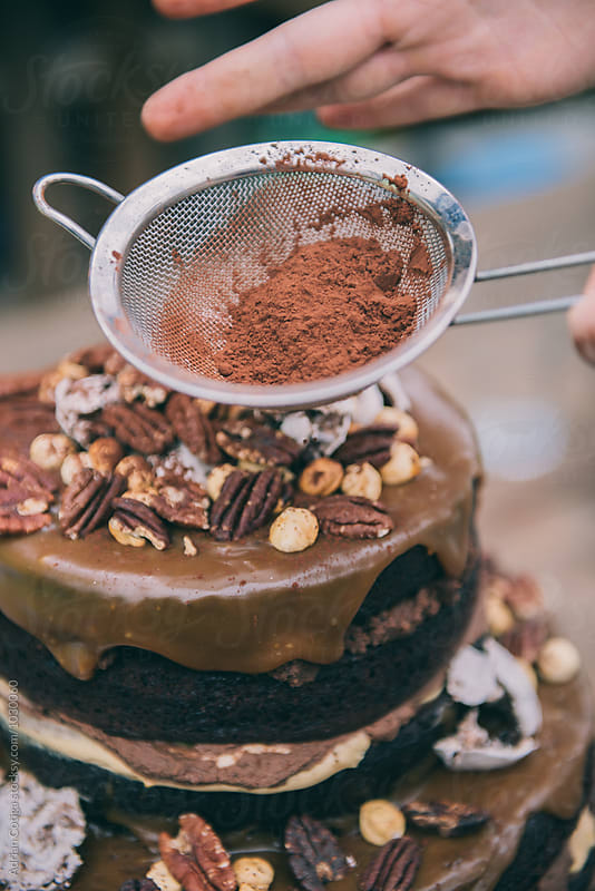Decorating Rustic chocolate cake with cocoa powder by Adrian Cotiga for Stocksy United