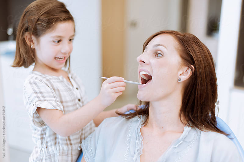 little girl playing to be a dentist with her mum by Guille Faingold for Stocksy United