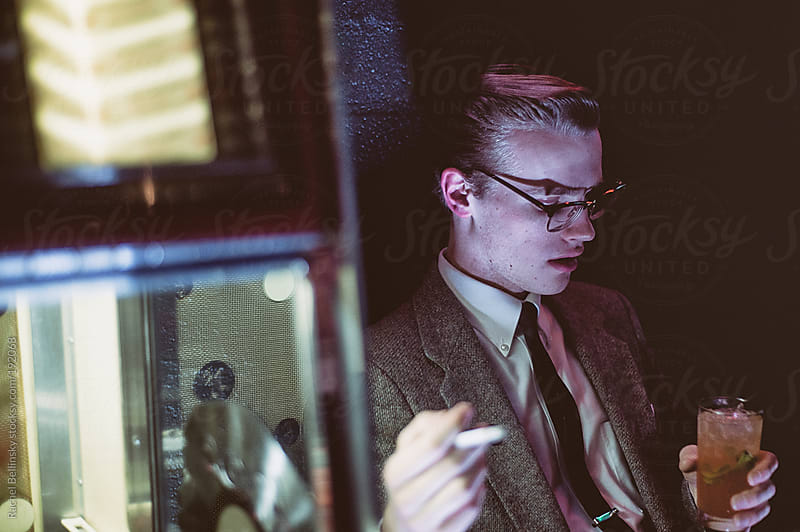 A dapper young man smokes and drinks by the jukebox by Rachel Bellinsky for Stocksy United