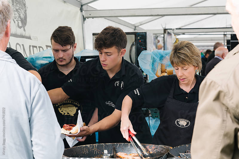 Busy market traders on takeaway hot food stall by Kirsty Begg for Stocksy United