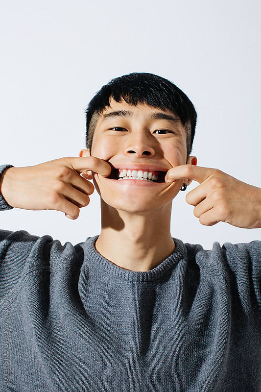 Portrait of a young asian man making funny face over white background.  by BONNINSTUDIO for Stocksy United
