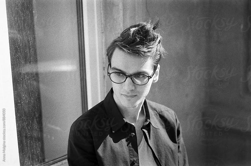 A black and white film portrait of a young beautiful man wih eyeglasses by Anna Malgina for Stocksy United