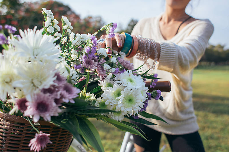 Spring time - closeup on a bicycle basket full of flowers by Jovo Jovanovic for Stocksy United