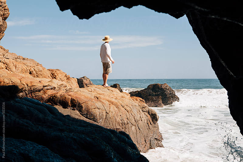 Man standing at entrance to sea cave, Pacific Ocean is distance by Paul Edmondson for Stocksy United