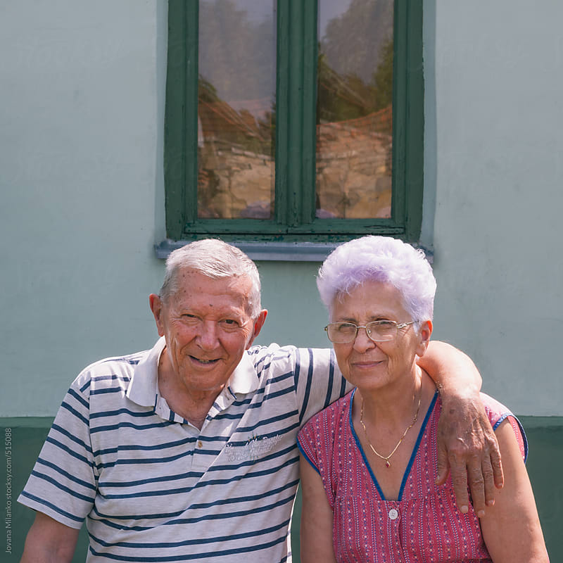 Senior couple hugged at the bench in front of their house by Jovana Milanko for Stocksy United