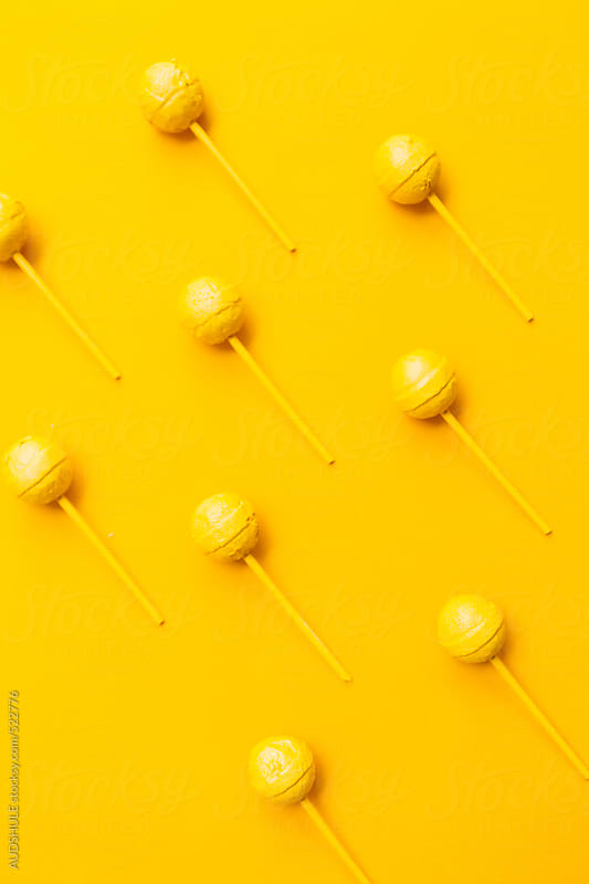 Minimalistic yellow lollipop on yellow background by Audrey Shtecinjo for Stocksy United
