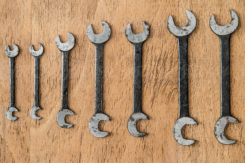 A set of old wrenches on a wooden background by Melanie Kintz for Stocksy United