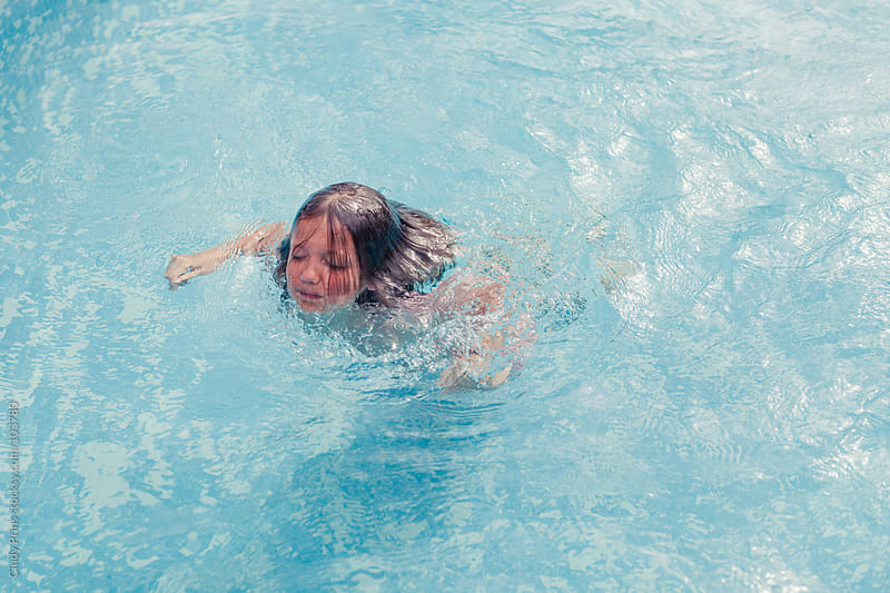 Boy in a swimming pool reaching the surface of the water by Cindy Prins for Stocksy United
