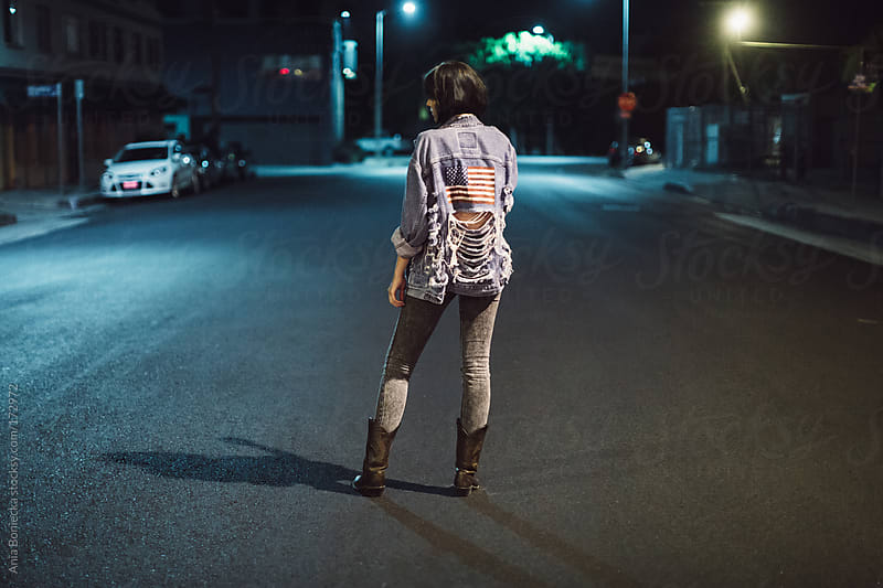 Girl standing in the street at night in a ripped denim jacket by Ania Boniecka for Stocksy United