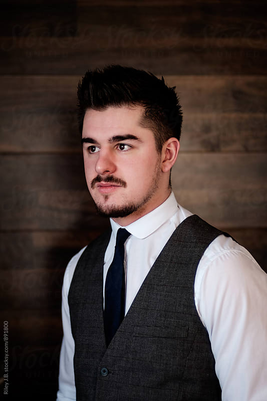 A portrait of a well dressed young man in front of a wood plank wall. by Riley J.B. for Stocksy United
