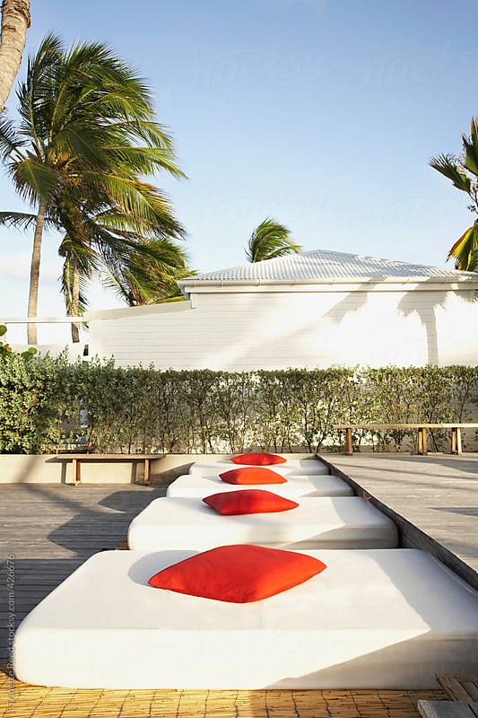 Lounge chairs with red pillows at luxury hotel  by Trinette Reed for Stocksy United