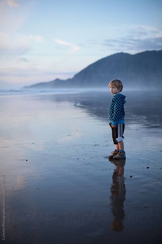 Boy stands on a beach at dusk by Carleton Photography for Stocksy United
