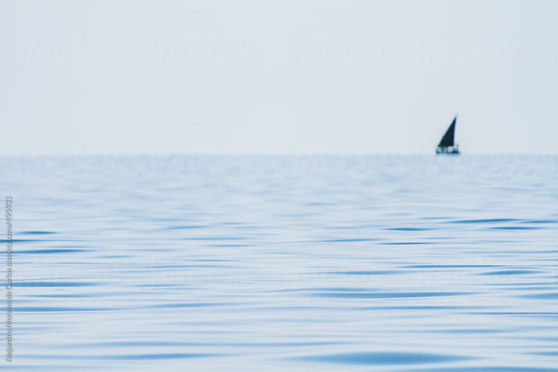 Sea detail with out of focus sailboat on the background by Alejandro Moreno de Carlos for Stocksy United