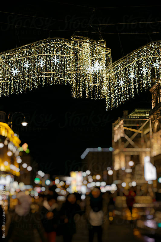 Christmas street lights and decor in the city by Beatrix Boros for Stocksy United