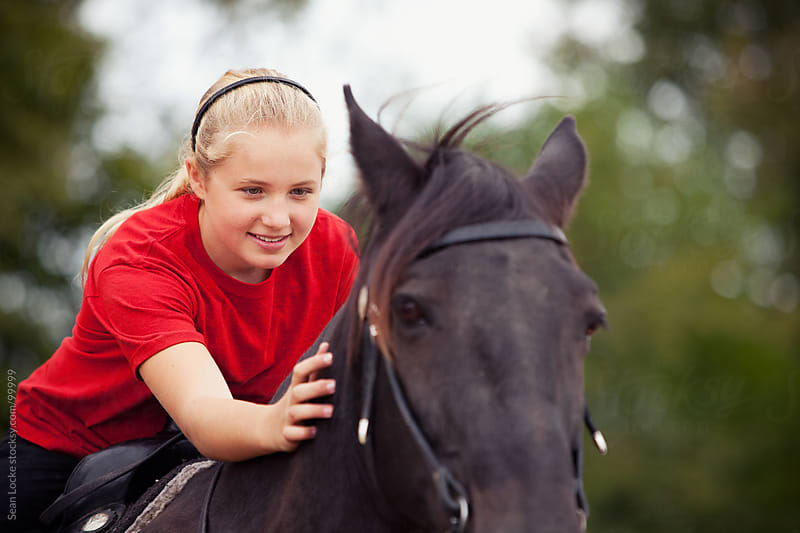 Equestrian: Girl Leaning to Pet Horse by Sean Locke for Stocksy United