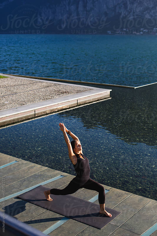 Woman doing yoga pose: Virabhadrasana I by michela ravasio for Stocksy United