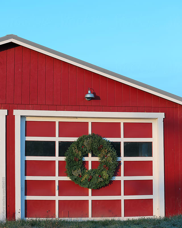 Christmas wreath on door of red barn by Daniel Hurst for Stocksy United