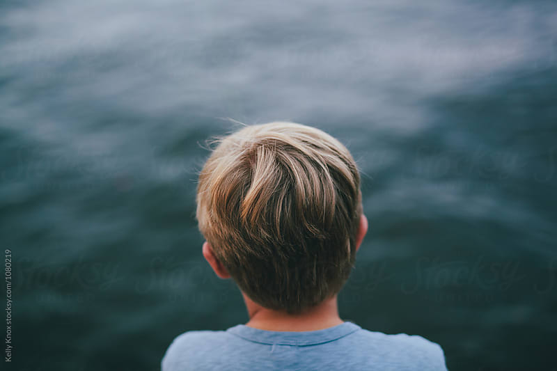 behind a boy looking out at a lake by Kelly Knox for Stocksy United
