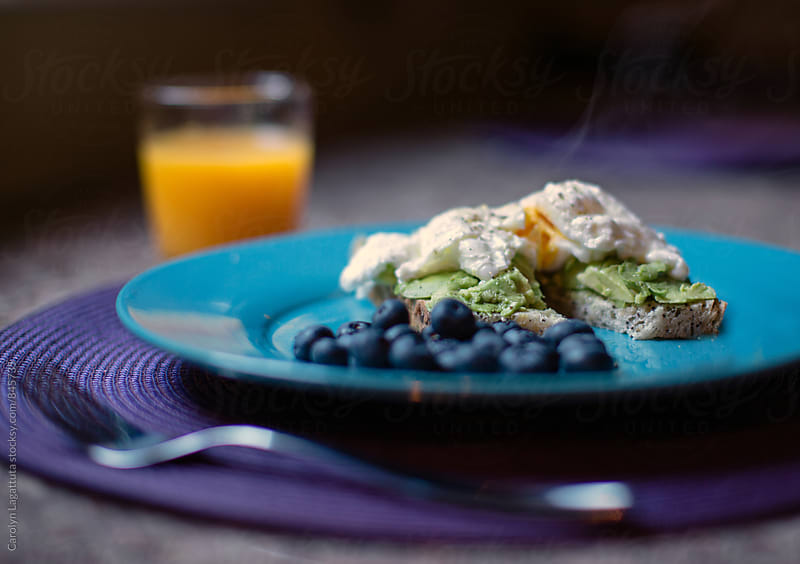 Poached egg on toast with avocado and blueberries by Carolyn Lagattuta for Stocksy United