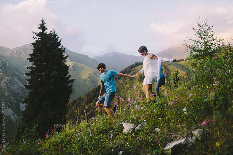 Young couple running down the mountain  by Evgenij Yulkin for Stocksy United