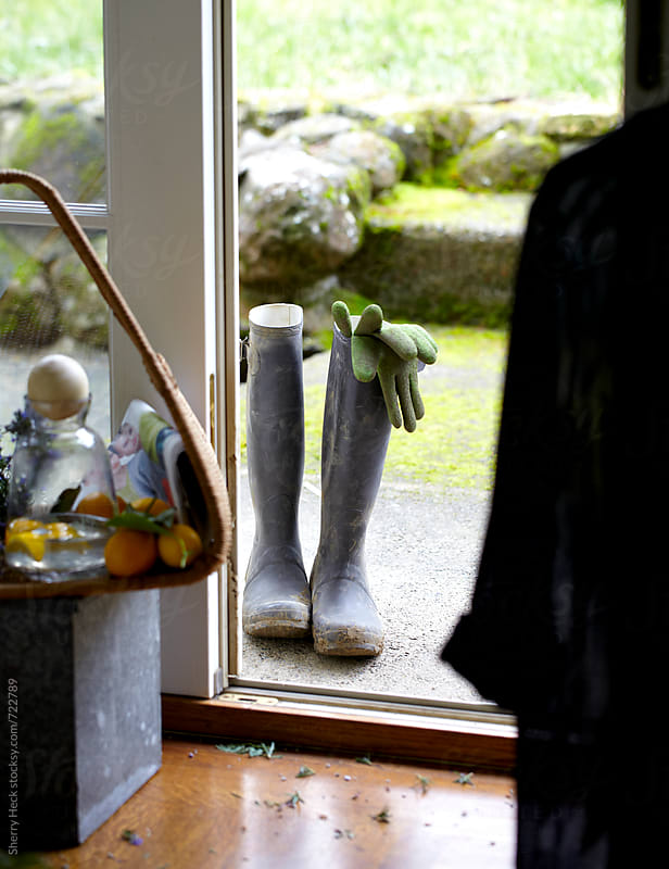 Rubber boots with gardening gloves in doorway by Sherry Heck for Stocksy United