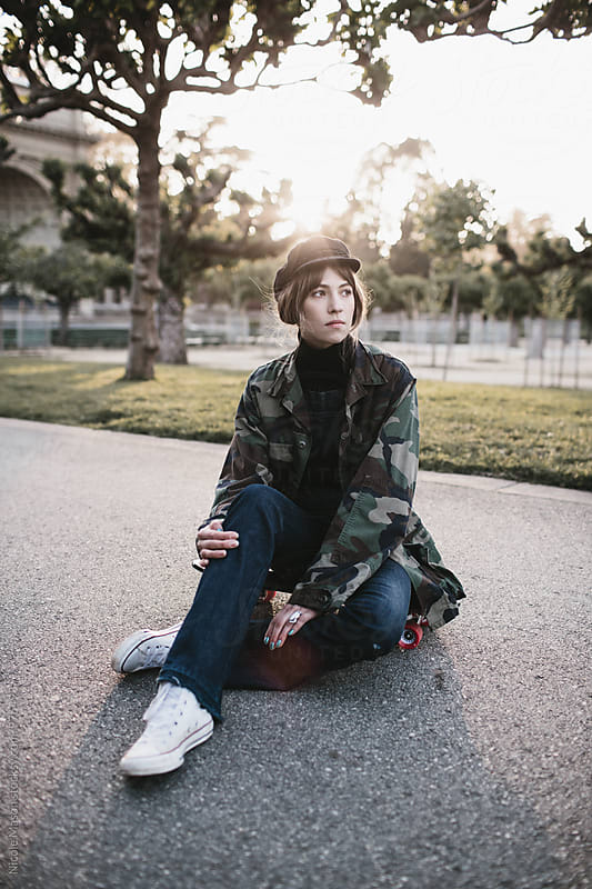 young woman sitting on skateboard in park at sunset by Nicole Mason for Stocksy United