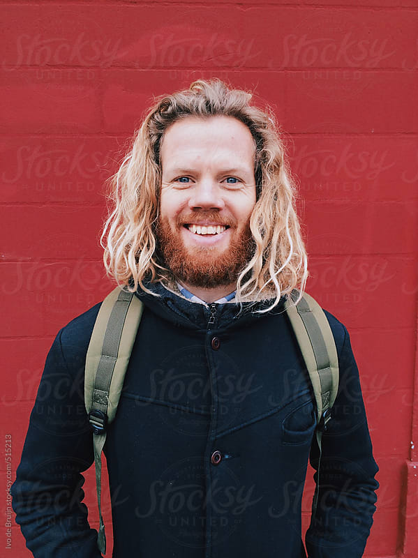 Young man with red hair standing in front of a red wall laughing at the camera, wearing a backpack by Ivo de Bruijn for Stocksy United