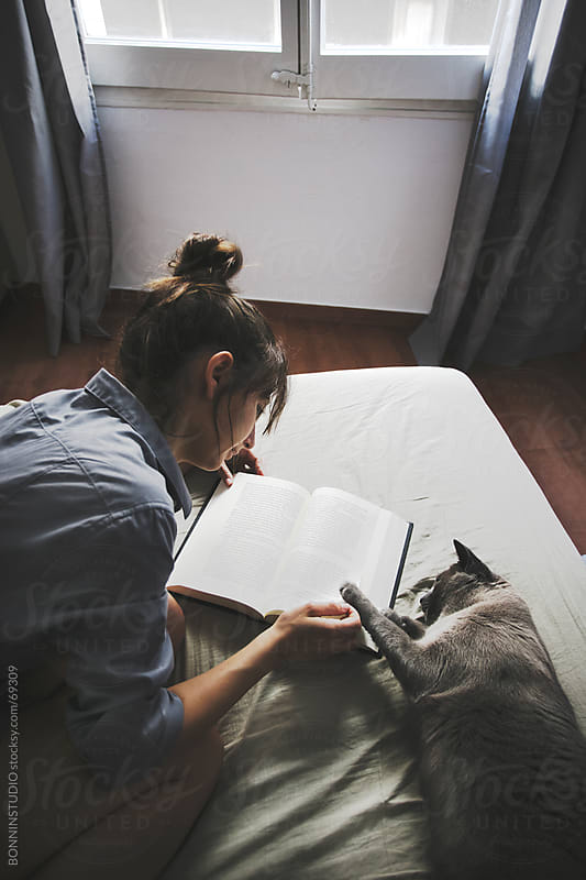 Young casual woman and her cat lying on the bed with coffe reading a book. by BONNINSTUDIO for Stocksy United