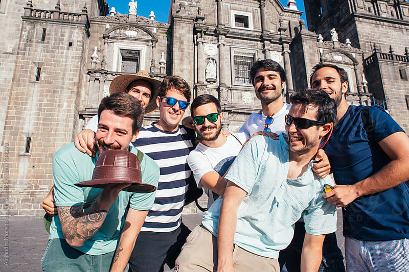 Group of young happy men in front of a cathedral on a sunny day by Alejandro Moreno de Carlos for Stocksy United