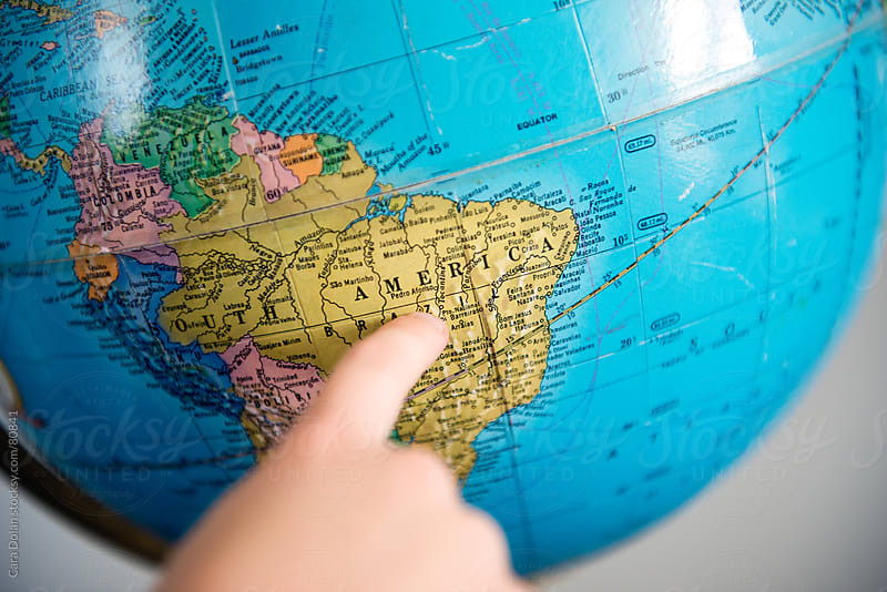 Child points to the country of Brazil on an old school globe by Cara Dolan for Stocksy United
