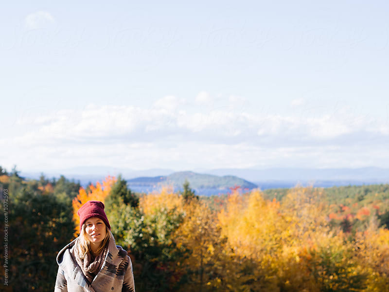 Young woman dressed for cold weather with autumn foliage and mountain by Jeremy Pawlowski for Stocksy United