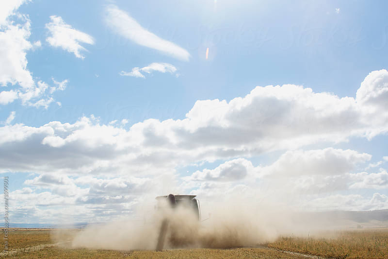dust surrounds moving combine by Tana Teel for Stocksy United