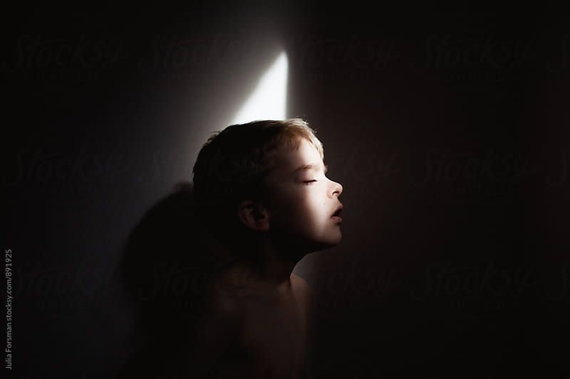 Profile of young boy in small batch of light in dark room. by Julia Forsman for Stocksy United