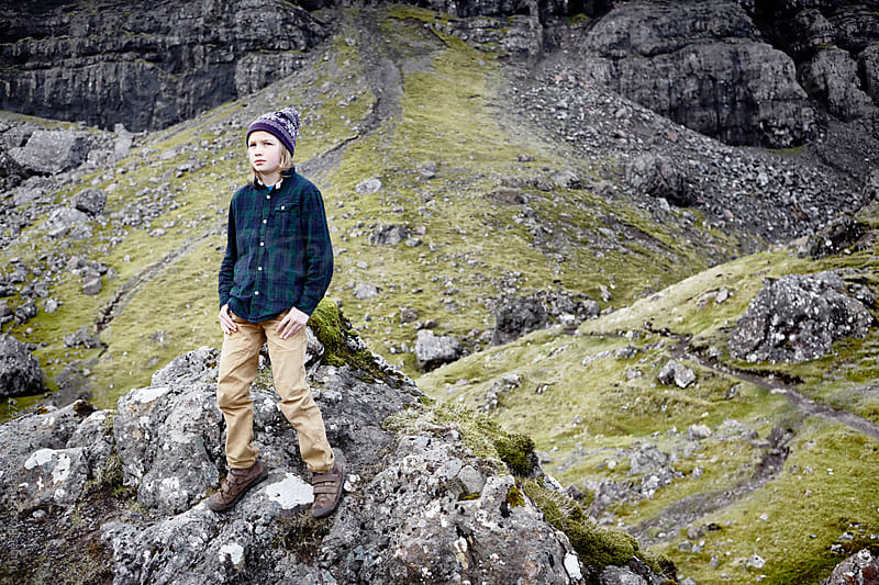 A young male standing on a rocky slope by James Ross for Stocksy United