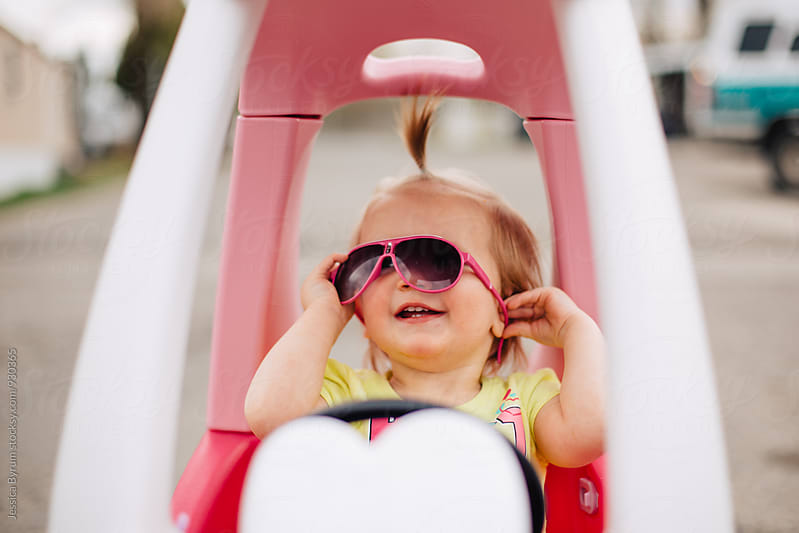 Toddler girl with sunglasses in pink toy car by Jessica Byrum for Stocksy United
