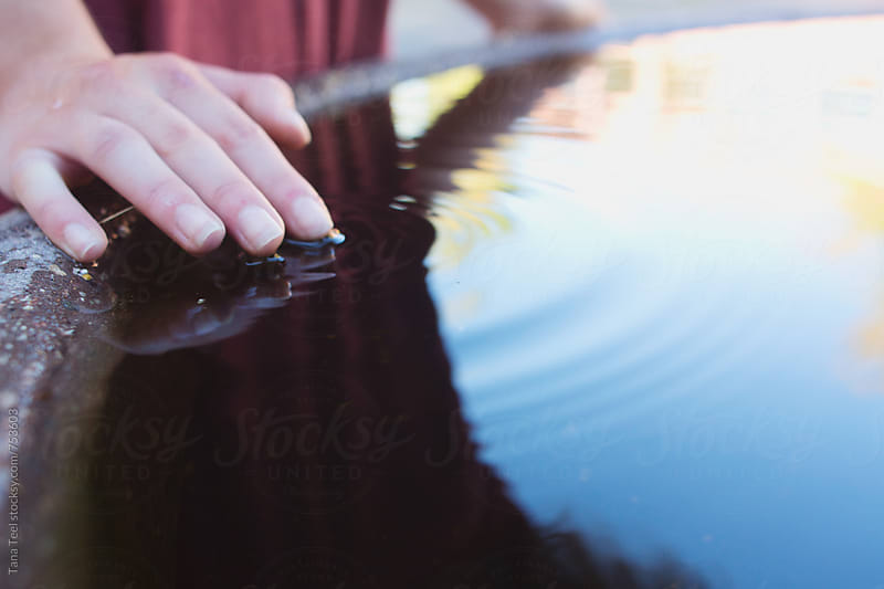 young woman's fingers make ripples in water fountain by Tana Teel for Stocksy United