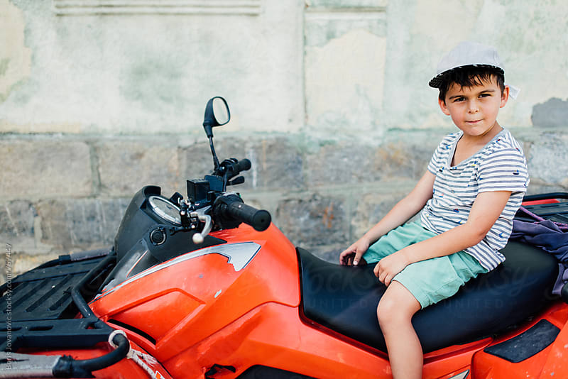 Boy sitting on a quad motoribike by Boris Jovanovic for Stocksy United