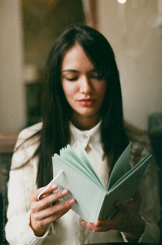 Young woman reading a notebook by Lyuba Burakova for Stocksy United