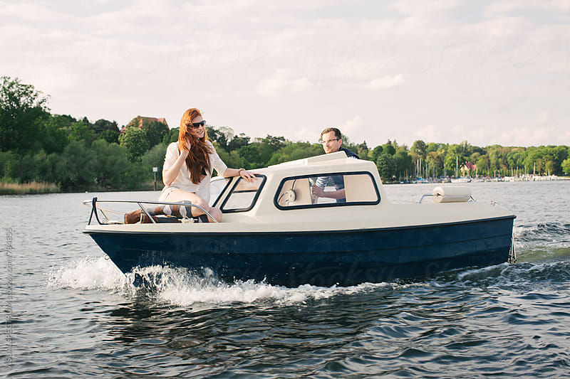 Good-Looking Caucasian Couple on Small Motorboat by Julien L. Balmer for Stocksy United