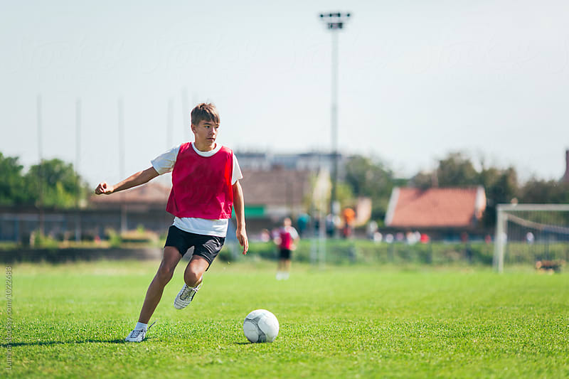 Boy Playing Football by Lumina for Stocksy United
