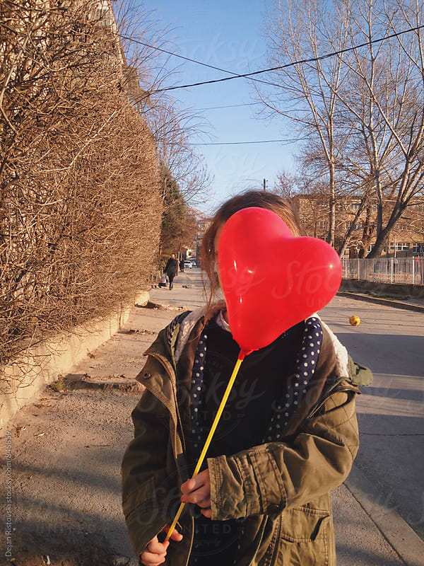 Little girl holding heart-shaped balloon  by Dejan Ristovski for Stocksy United