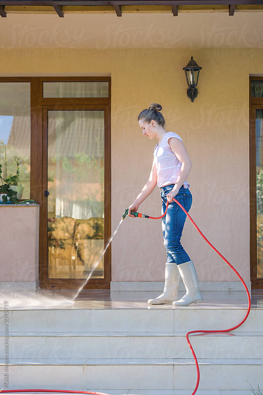 Young woman washing the terrace with a garden hose by RG&B Images for Stocksy United