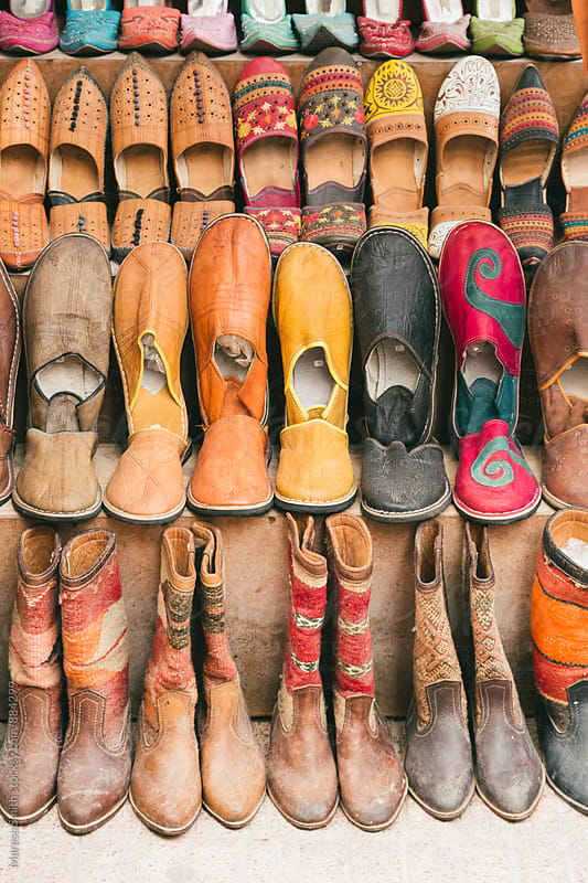 Moroccan slippers and boots stacked up at a market stall in Essaouira  by Maresa Smith for Stocksy United
