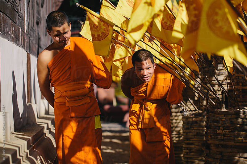 Young Buddhist monks walking out of the temple by michela ravasio for Stocksy United