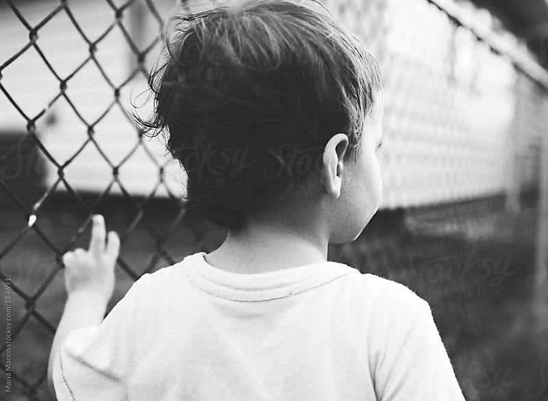 boy leans against fence by Maria Manco for Stocksy United