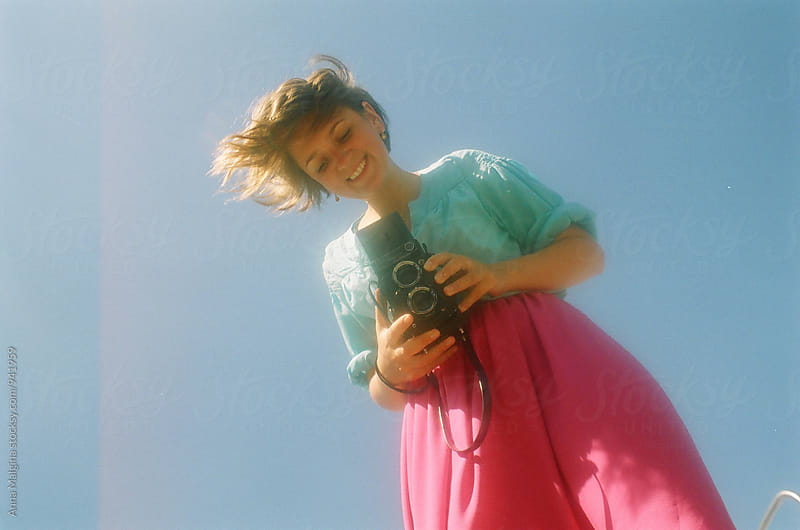 A film portrait of a young beautiful smiling woman taking photo by Anna Malgina for Stocksy United