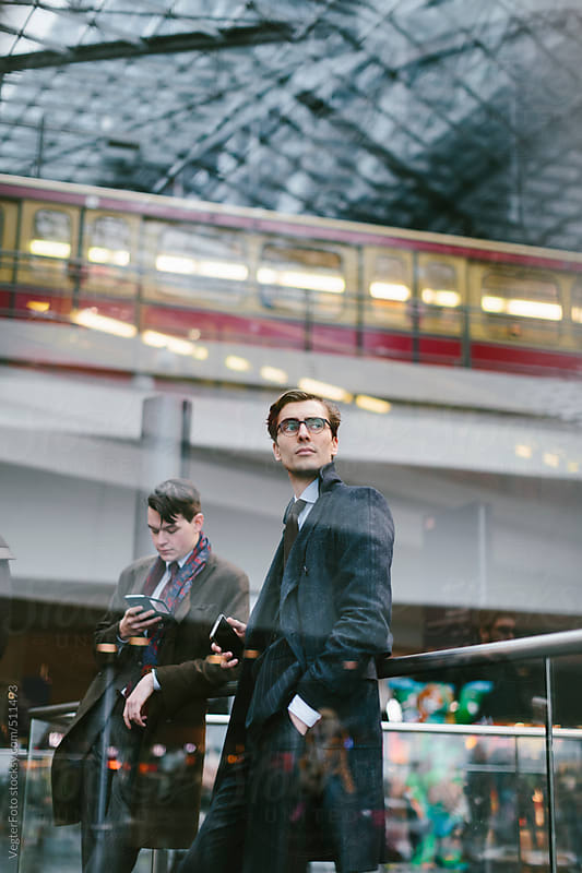 Businessmen With Smart Phone Waitng At Train Station by VegterFoto for Stocksy United