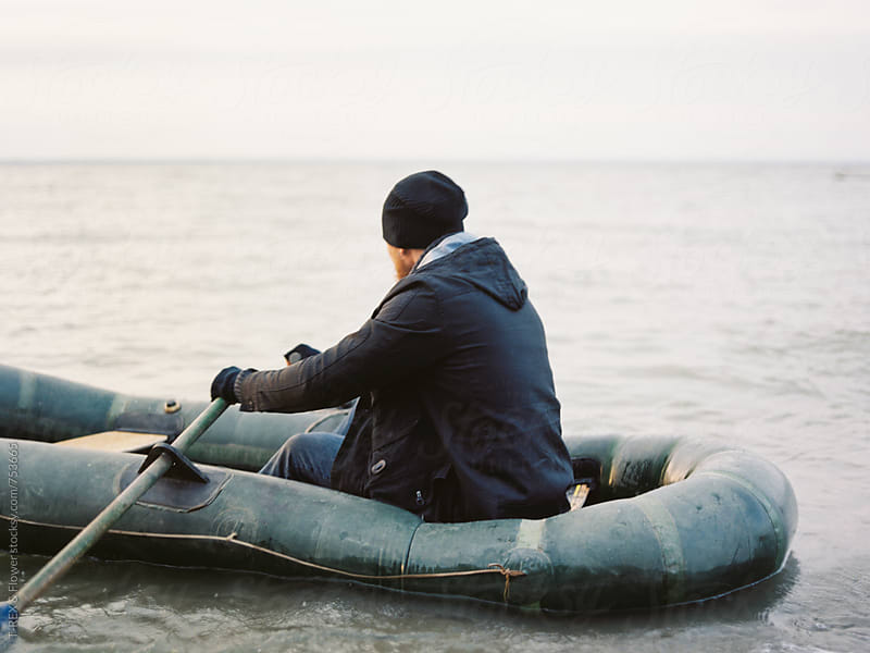Man in row boat. Film by Danil Nevsky for Stocksy United