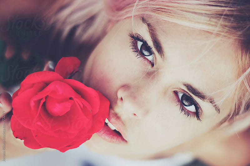 Beautiful girl holding rose in her hand by Jovana Rikalo for Stocksy United