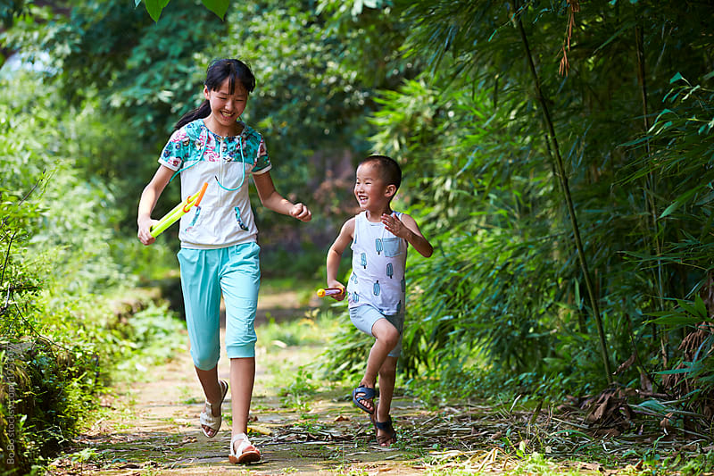 Lovely little girl with her brother outdoor by cuiyan Liu for Stocksy United